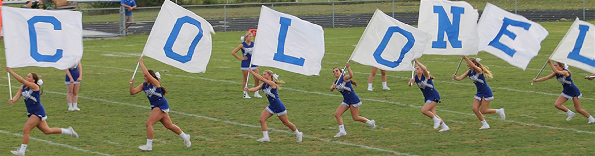 OCHS Cheerleaders running with COLONEL flags